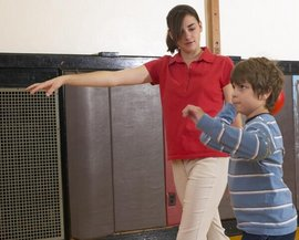 Graduate student works with an elementary student on physical fitness