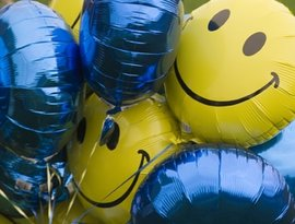 Happy face balloons in IC colors welcome alumni to events