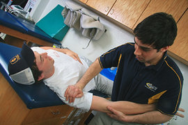 Jason Edelstein '08 works with an athlete who has experienced a shoulder injury.