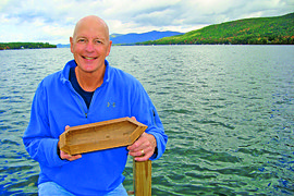 Joseph W. Zarzynski '73, on Lake George, holds a model (sans mast and oars) of the 1758 Land Tortoise. Photo by Peter Pepe.