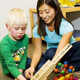 Karen Yoshido '10 works with an autistic child.