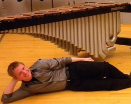 Laying in front of a marimba