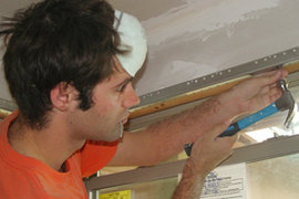 Lucien DeLaBruere '09 hammers drywall into Pastor Bruce and Deborah Davenport's home in the 7th Ward of New Orleans. Photo courtesy of the author.