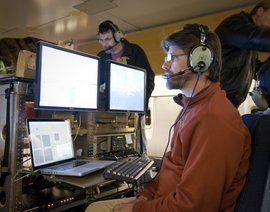 Luke Keller operates the FORCAST camera onboard SOFIA while Cornell University astronomer Terry Herter (background), who leads the FORCAST team, analy
