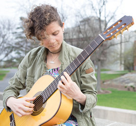 Madeline Docimo '15 plays her guitar on campus. Photo by Adam Baker