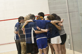Members of the newly formed squash team huddle up before a game.