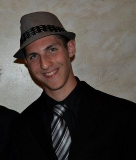 Michael Falconieri in a black suit, silver and black striped tie, and grey fedora
