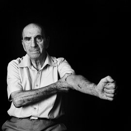 Photo from the film Numbered of a survivor of Auschwitz with his tattooed number on his arm