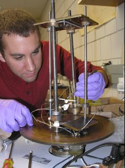 Physics student Justin Sousa (wearing nice purple gloves) loads gold into the metal evaporator