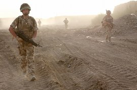 Soldiers in Iraq patrolling a dusty road.