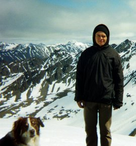 Student hiking in snowy mountains with dog