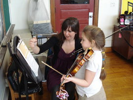 Student teacher instructs young violinist