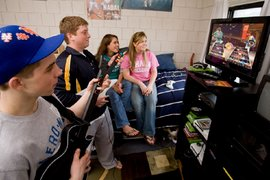 Students enjoy a video game in their dorm room
