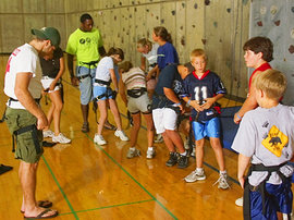 Students help young campers prepare to use Ithaca\'s climbing wall.