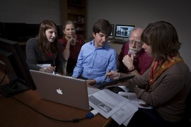 Students in a class review their iPad app project with faculty