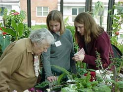 Students with residents in Longview greenhouse
