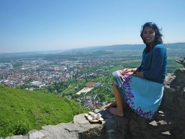 Suellen sittint on a rock on top of a mountain