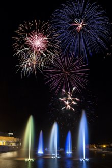 The fountains at IC glow in multiple colors while fireworks burst overhead.