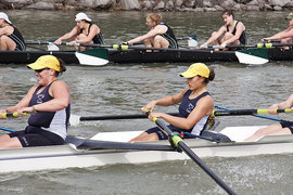 The women's crew team rows hard at a home race.