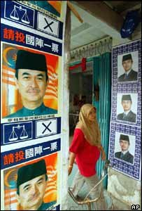 Woman walks past election campaign posters of Malaysian Prime Minister Abdullah Ahmad Badawi (BBC Photo; 2004)