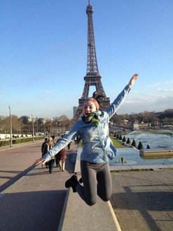 student jumping in front of Eiffel Tower