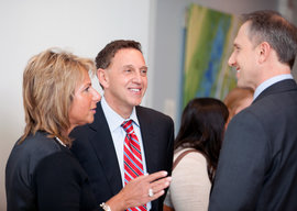 two men and a woman chatting at a reception