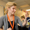 Emily Brown '12 shares a high-five with a student in the classroom.